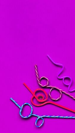 Multicolored Drinking Straws In A Festive Pattern on blue background Imagens