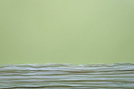 The texture of background picture the olive and sage green corrugated fabric with parallel or diagonal folds on paper. Blank for design, backdrop, concept of nature, springtime, fresh greenery.