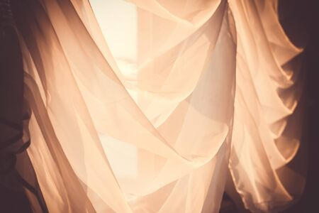 Elegant, thin transparent curtain on the window, by sunlight. Vintage toned photo. Selective soft focus.