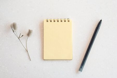 White marble table, on it is a yellow blank notebook with a spiral for notes, pen, fluffy flower. Cozy home workplace freelancer.