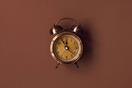 Old mechanical alarm clock on brown background. Minimalistic composition with one object
