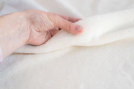 Female hand touches a soft cozy plaid of white fabric with a pile. Textile material, pleasant to the touch