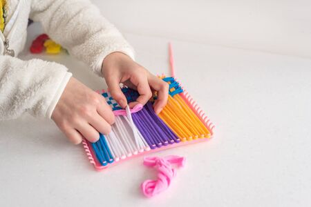 childrens creativity weaving with colored threads ropes. Child hands in work on white table.