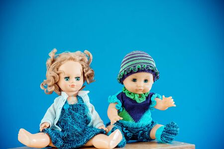 Two Old-Fashioned baby Dolls dressed in knitted costume sits on shelf on blue background