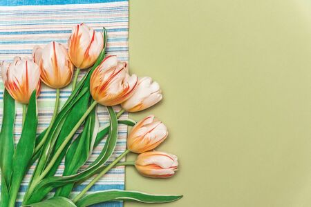 Composition with a bouquet of beautiful tulips on a towel. The concept of spring family cozy home holidays, spring time.
