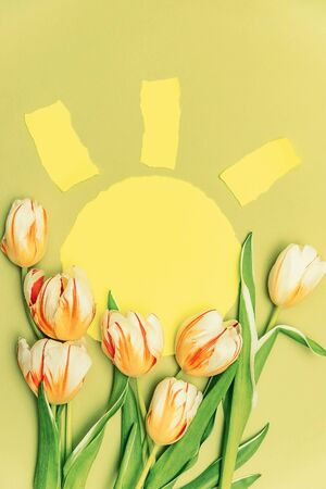 Composition with yellow sun and a bouquet of beautiful tulips. The concept of spring holidays, spring time. Copy space. Stock Photo