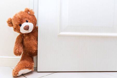 Teddy bear with brown hair behind open door. Background for kids play with plush toy. Copy space on white doors. Standard-Bild