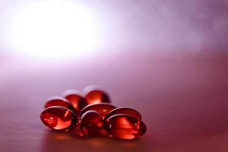 Vitamin capsule or Omega 3 capsules on pink background Fish oil red softgels Vitamin D, E, A Stock Photo