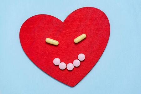 Medicine pills and Capsules on red heart shape from anthropomorphic smiling face. Medical concept Stock Photo