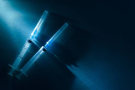 Two disposable syringes close up shot on a dark blue dramatic light backdrop. Vaccination and virus protection concept. 写真素材
