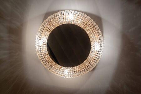 Close up view of beautiful crystal chandelier round shape hanging from the ceiling in the interior of room hotel. Large crystal chandelier glass refracts and reflects light Stock Photo