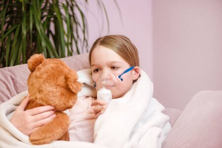 Respiratory inhalation, personal care, hospital. Kid girl, asthma problem. Little girl Sitting with a toy on the couch in a mask for inhalations, making inhalation with nebulizer at home inhaler.