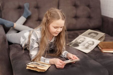 Young Girl lie on sofa and looking at old family photo album. 版權商用圖片 - 143283959