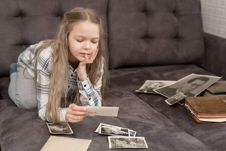 Young cute Girl sits on sofa and looking at old family photo album.