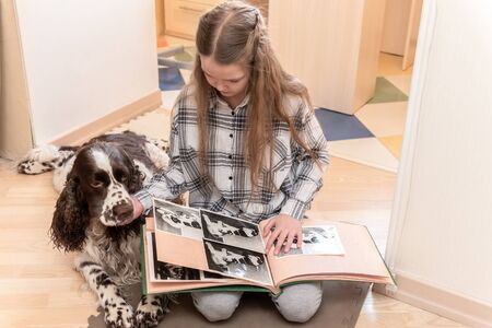 Young Cute girl looking photo album with her dog at home on the floor.