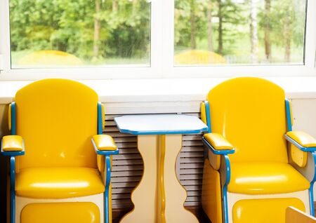 Living room: Chairs, table and toys. Interior of kindergarten.