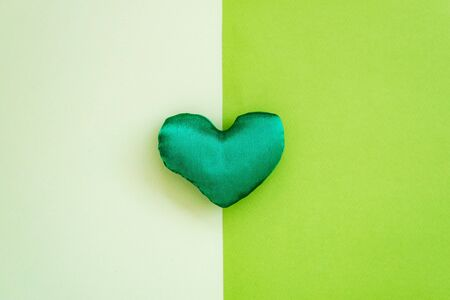 Lovely green handmade fabric heart shaped on colored textured paper background.