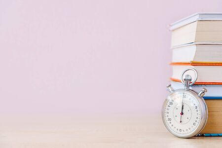 Stack of many books and stopwatch on simple backdrop. Copy space for your text.