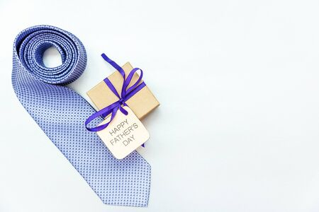 Happy Father's Day inscription with tie and gift box on white background. Greetings and presents