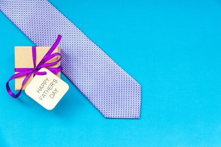 Happy Fathers Day inscription with tie and gift craft box on blue background. Greetings and presents Zdjęcie Seryjne