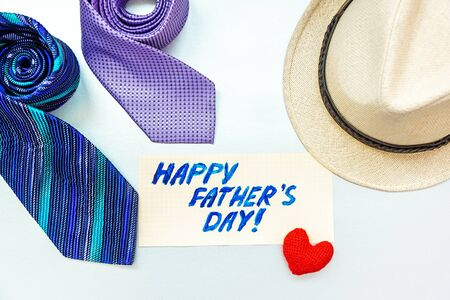 Happy Father's Day inscription with ties, hat and gift box on white background. Greetings and presents Zdjęcie Seryjne