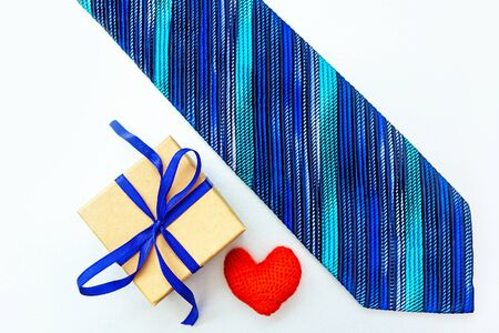 Handsome mans tie, red heart and craft box with a gift on white background with place for your text. Blank for greeting card design.