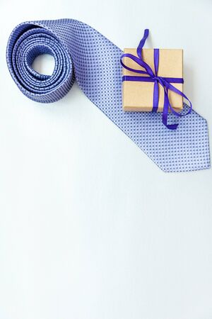 Handsome blue mans tie and craft box with a gift on a white background with place for your text. Blank for greeting card design.