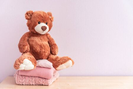 Teddy bear sits on Stack of winter or autumn womens clothes. Pile of rose knitted cozy warm pink sweaters or pullover on wooden table.