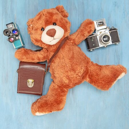 A stuffed toy teddy bear lies and holds old photo camera and retro video camera on a blue wooden