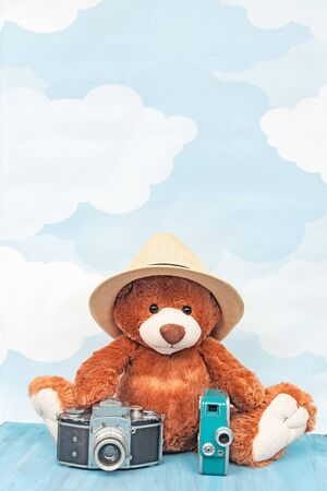帽子のぬいぐるみのテディベアは、青い空のパステルの背景に古い写真カメラとレトロなビデオカメラの近くに座っています。バックグラウンド。 写真素材