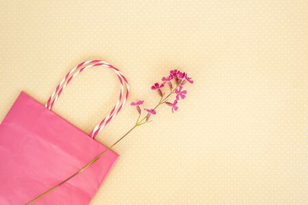 Purple wild flower and pink shopping bag on yellow paper.. Concept of seasonal summer discounts. Фото со стока