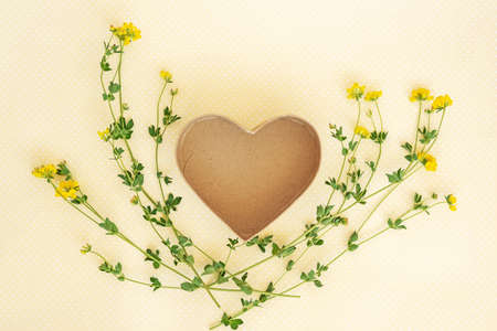 Creative layout made of flowers and leaves with heart shaped gift box. Flat lay. Nature concept.