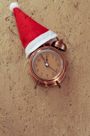 Retro style alarm clock with red christmas santa claus hat on golden wooden texture background with copy space. Vertical photo