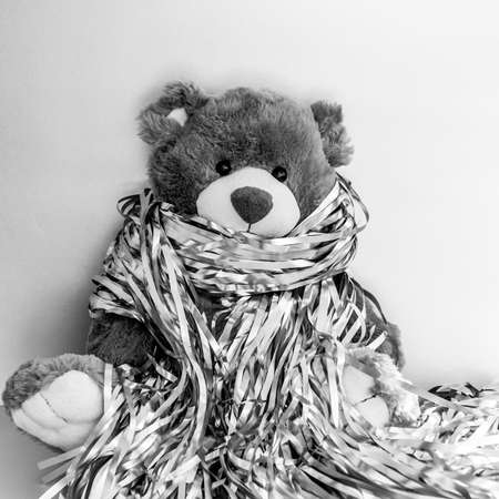 Christmas composition with stuffed toy teddy bear. Black and white square photo