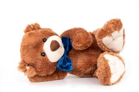 Adorable stuffed toy with blue ribbon bow on neck. Plush bear laying isolated, calm and relaxed. Plaything for children, present for holidays, gift for Valentines day. Cuddly and soft doll for playing Banco de Imagens