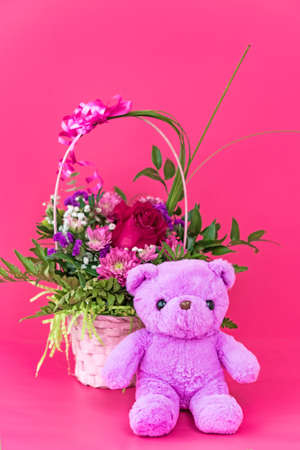 Funny lilac teddy bear with basket of flowers sitting on pink studio background. Cute greeting postcard for women's day or happy birthday. Holiday surprise concept