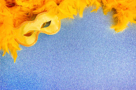 Yellow carnival mask and feather boa on blue texture background with copy space. Blank for a holiday cardon on mardi gras, congratulations. Photo for a theater poster or children's acting school.