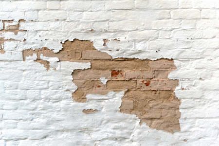 Surface of old wall of weathered bricks with white stucco