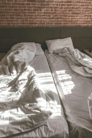 Loft style of bedroom, unmade beds with blankets 版權商用圖片