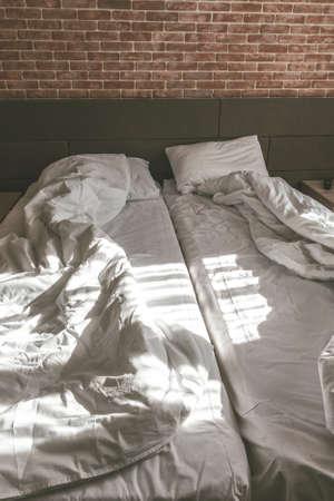 Loft style of bedroom, unmade beds with blankets Standard-Bild