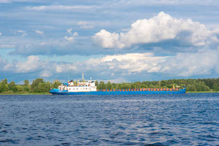 Shipping boat floating on river or lake calm view Standard-Bild