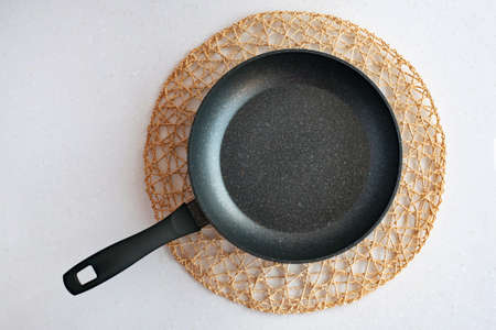 Frying pan on woven napkin, flat lay kitchenware