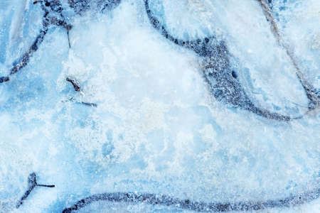 Surface of natural ice covering on water in winter. Ice texture with intersperses of frost, crystals of frozen water.