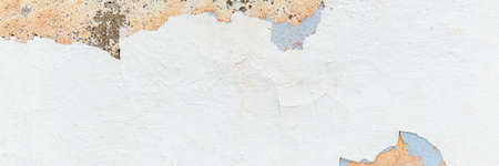 Weathered building wall with white chipped stucco closeup