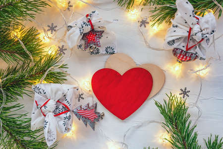 Christmas gift decorated with fir branch and garland light and red heart on white Standard-Bild