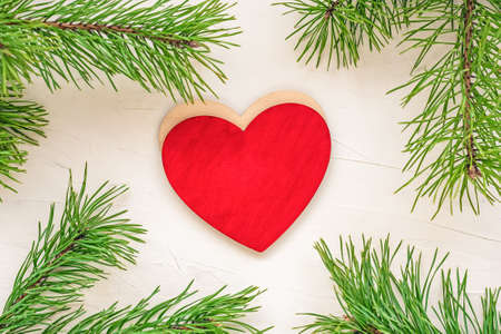 Xmas greeting card with red heart and green branches christmas tree Standard-Bild