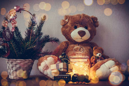 Christmas card with big and small Teddy bear, present gift box on toy locomotive, decorated christmas tree, fairy lights garland in a glass jar on bokeh background.
