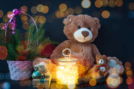 Greeting xmas card with  bear doll , gifts and fairy lights garland. Standard-Bild