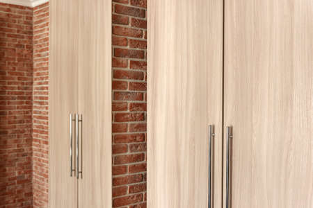 Wooden wardrobe reflected in large mirror on red brick wall Standard-Bild