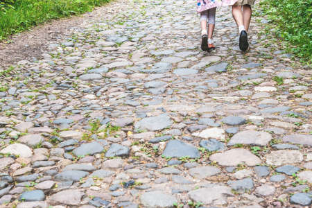 Young couple walk along old rural road with rocks and grass